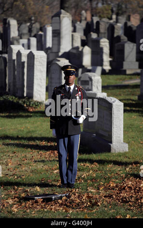 An Army soldier stands in the Cypress Hills National Cemetery waiting to play taps. - Stock Photo