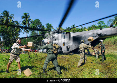 U.S. Airmen and Marines unload relief supplies from a CH-53E Super Stallion helicopter in Indonesia. - Stock Photo