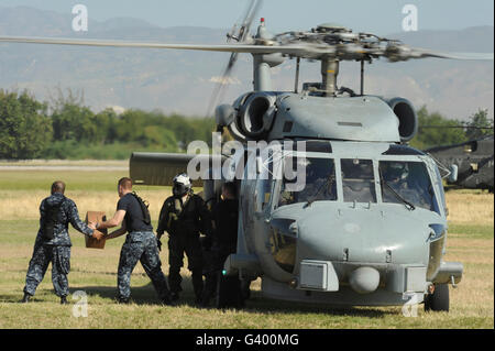 U.S. Navy sailors load humanitarian supplies onto a Navy HH-60 Pave Hawk helicopter. - Stock Photo