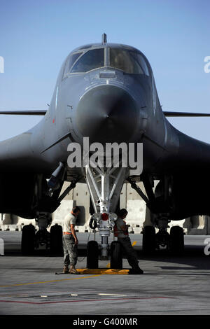 Crew chiefs wait for a B-1B Lancer aircrew to accomplish system checks prior to takeoff. - Stock Photo