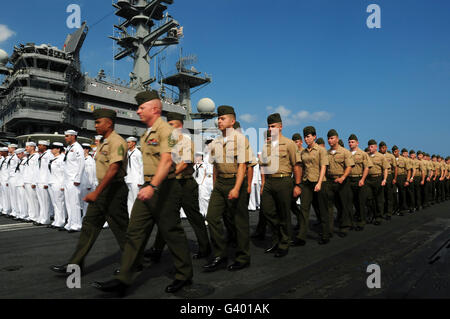 U.S. Marines march in formation to move into position to man the rails with sailors aboard USS Ronald Reagan. - Stock Photo