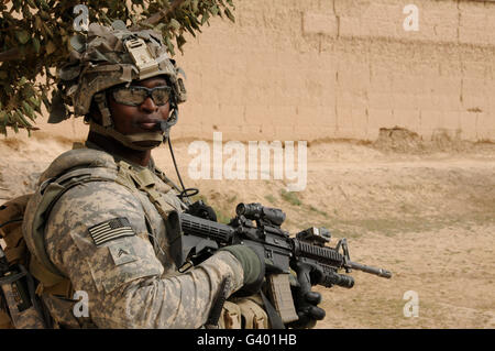 U.S. Army soldier scans his area while on patrol in Afghanistan. - Stock Photo