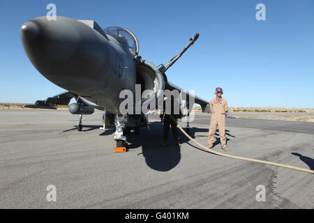 U.S. Marine Corps air crewmen refuel an AV-8B Harrier II aircraft. - Stock Photo