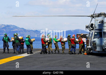 Sailors and Marines load supplies onto a HH-60H Seahawk. - Stock Photo