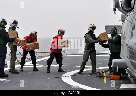 Sailors load boxes of food onto an SH-60F Sea Hawk helicopter. - Stock Photo