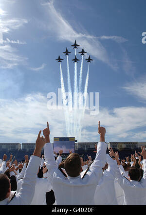 Members of the U.S. Naval Academy cheer as the Blue Angels perfom during graduation. - Stock Photo