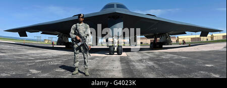 An Airman guards a B-2 Spirit at Ellsworth Air Force Base. - Stock Photo