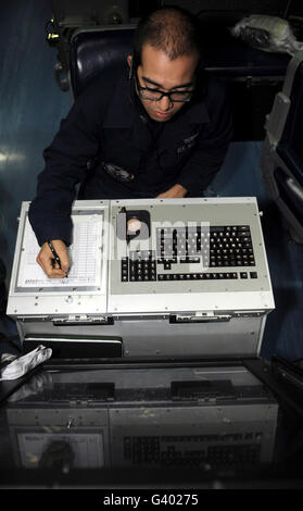 Air Traffic Controller records incoming aircraft inside the control center aboard USS John C. Stennis. - Stock Photo