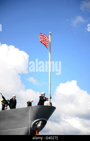 A Sailor raises the First Navy Jack on the flagstaff of USS Monterey. - Stock Photo