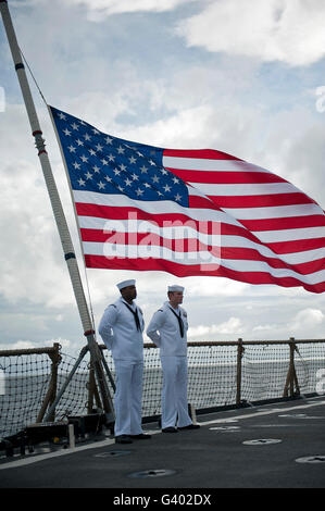 Sailors stand at parade rest during a remembrance ceremony aboard USS Pearl Harbor. - Stock Photo