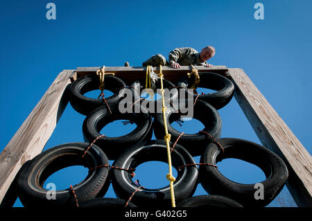 A soldier climbs over a tire tower on an obstacle course. - Stock Photo