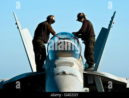 U.S. Navy sailors wipe down the canopy of an F/A-18F Super Hornet. - Stock Photo