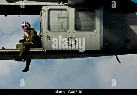 A U.S. Navy naval air crewman guides the pilots of an MH-60S Knighthawk.