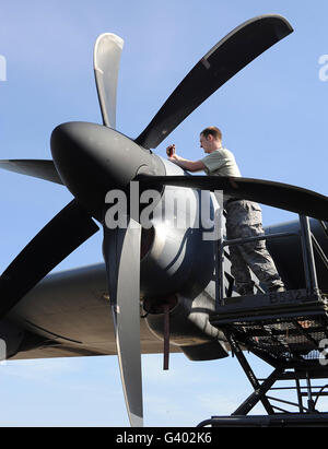 Mechanic finishes moving an engine propeller on a C-130J Super Hercules. - Stock Photo