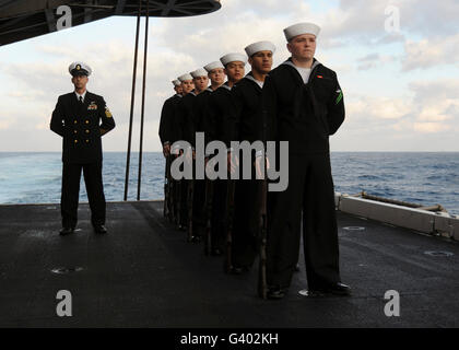 The honor guard stands at parade rest during a burial at sea. - Stock Photo