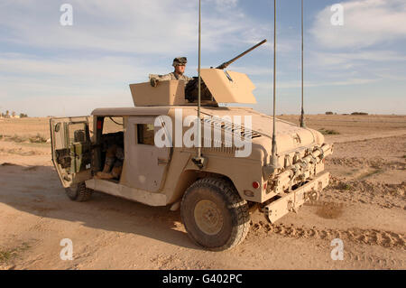 U.S. Army soldier pulls security on top of a M1114 Armored HMMWV - Stock Photo