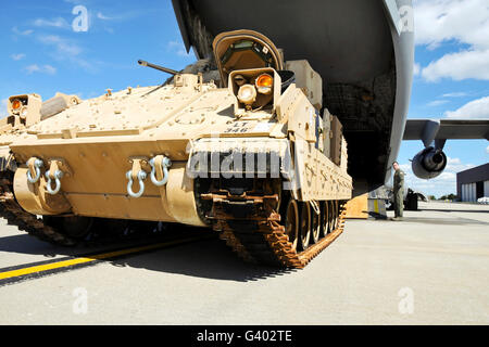 An M2/M3 Bradley fighting vehicle drives toward a C-17 cargo bay. - Stock Photo