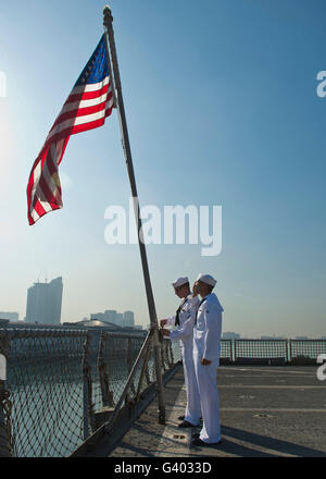 Seamen participate in morning colors on the flight deck of USS Tortuga. - Stock Photo