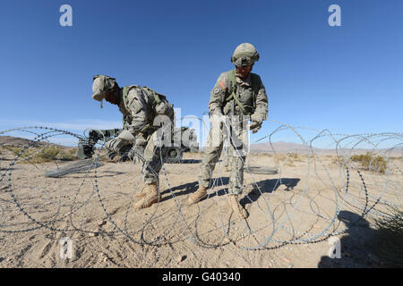 Soldiers uncoil concertina wire at Fort Irwin, California. - Stock Photo