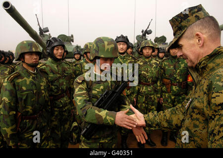 Chairman of the Joint Chiefs of Staff shakes hands with Chinese tanker soldier. - Stock Photo
