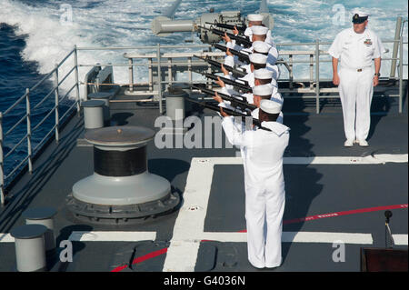 Sailors render a rifle volley aboard USS Hue City. - Stock Photo