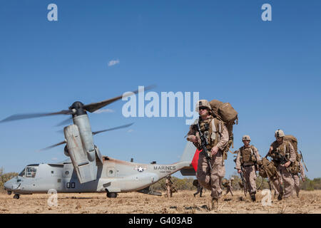 Marines and Sailors offload from a MV-22 Osprey. - Stock Photo
