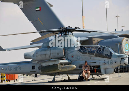 U.S. Marine takes a break sitting on an AH-1Z Cobra attack helicopter.