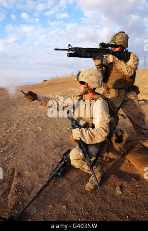 A Marine fires a M203 grenade launcher while fellow Marine fires a pin flare. - Stock Photo