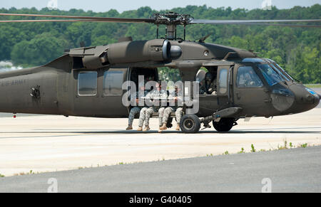 National Guard Special Forces Soldiers sit with their legs hanging outside of a UH-60. - Stock Photo