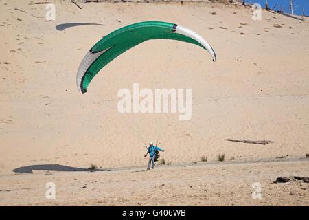 Paraglider landing on beach Dune of Pyla Southern France - Stock Photo