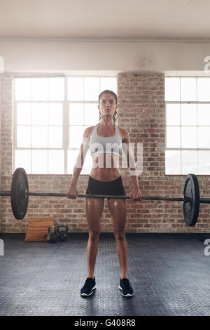 Fit young female athlete lifting heavy weights. Fitness  model performing crossfit exercise at gym. - Stock Photo