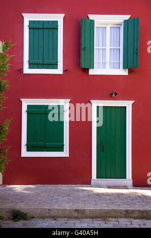Green shutters on a red wall, in Nafplio, Greece - Stock Photo
