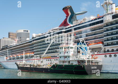 Refuelling tug alongside 'Carnival Legend' cruise ship berthed at Circular Quay, Sydney, New South Wales, Australia - Stock Photo
