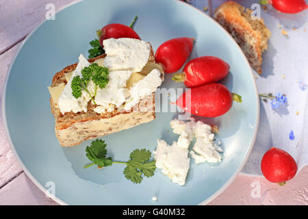 Fresh healthy breakfast, a slice of soda bread with butter and cottage cheese and red radish - Stock Photo