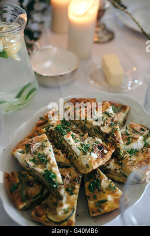 Frittata with vegetables and goat cheese and a glass jar of lemon and lime infused water on a set up table for light - Stock Photo