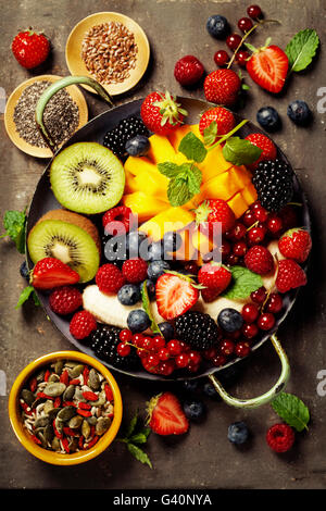 fresh summer fruits and berries on plate, above, rustic background - Stock Photo