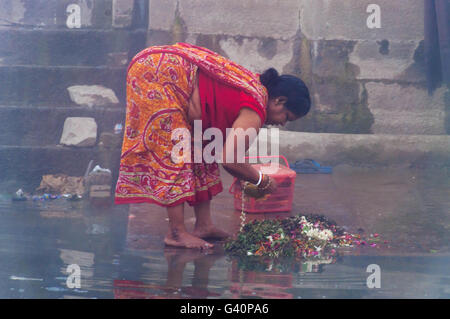 Unidentified Indian woman taking ritual bath in the river Ganges at cold foggy winter morning. - Stock Photo