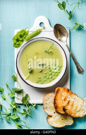 Light summer green pea cream soup in bowl with sprouts, bread toasts and spices. White ceramic board in the center, - Stock Photo