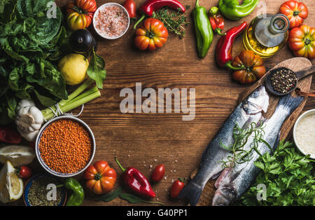 Ingredients for cooking healthy dinner. Raw uncooked seabass fish with vegetables, grains, herbs and spices over rustic wooden b