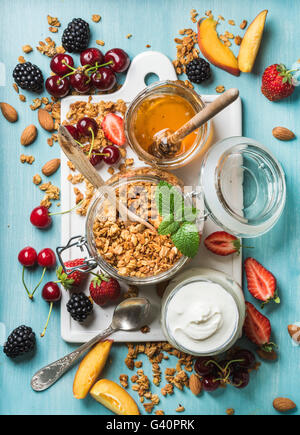 Healthy breakfast ingredients. Oat granola in open glass jar, yogurt, fruit, berries, honey and mint on white ceramic - Stock Photo