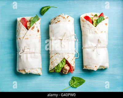 Healthy lunch snack. Tortilla wraps with grilled chicken fillet and fresh vegetables on blue painted wooden background. - Stock Photo