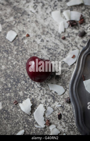 Single cherry and coconut flakes on grey background - Stock Photo
