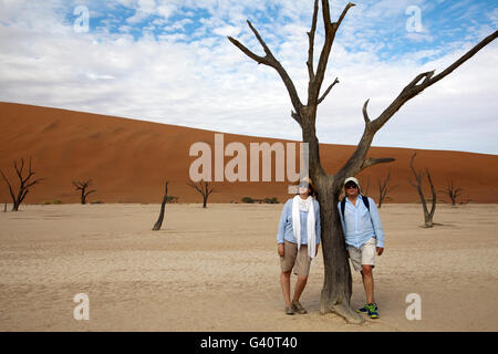 Visitors Pose Against Dead Acacia Tree in Deadvlei in Sossusvlei in Namibia - Stock Photo