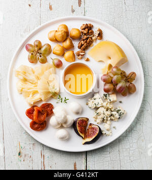 Cheese plate Snacks assortment with honey on white plate - Stock Photo