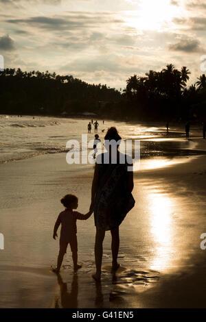 Sri Lanka, Mirissa beach, mother and child in last rays of evening sun - Stock Photo