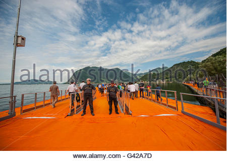 Lake Iseo, Italy. 18th June, 2016. Volunteers check visitors on the gate of The Floating Piers of Christo on June - Stock Photo