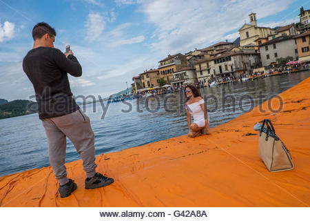 Lake Iseo, Italy. 18th June, 2016. A couple take pictures on The Floating Piers of Christo on June 18, 2016 in Lake - Stock Photo