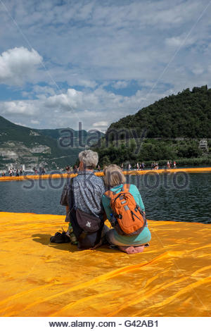 Lake Iseo, Italy. 18th June, 2016.  People seat on The Floating Piers of Christo on June 18, 2016 in Lake Iseo, - Stock Photo