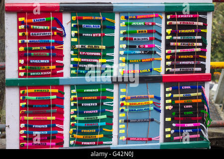 Variety of colourful handwoven word bracelets kept for sale - Stock Photo