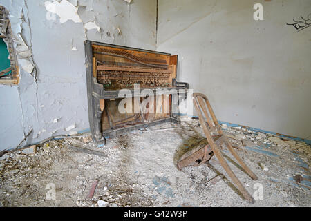 broken piano and chair in abbondoned house Lesvos Greece - Stock Photo